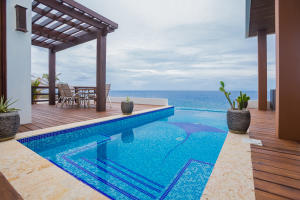 The infinity edge pool, complete with mosaic Eagle Ray, blends seamlessly with the Caribbean Sea