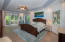 This spacious master bedroom has a garden view and steps out onto the pool