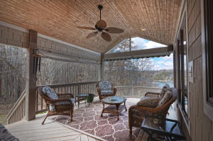 Covered porch is just off dining room and overlooks the lake