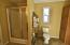 Shower, comode area includes a tall storage cabinet & window!