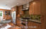 Gorgeous galley kitchen with stainless appliances, lovely cupboards and custom counter / tile backsplash