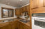The kitchen offers a galley style with wood cupboards and a double sink.