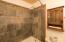 This custom bathroom offers slate tiles and vintage style hardware.