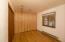 The second bedroom offers a wood accent wall, windows to the south, new paint, and refinished solid wood floors.