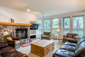 The great room is surrounded by windows and filled with natural light.