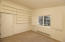 Bedroom offers custom shelves, windows with wood shutters, high ceilings and fresh paint