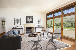 A beautiful, modern take using Virtual Staging of the main floor living room. The white walls, wood accents & floor to ceiling windows offer an easy transition to any style of furnishings.