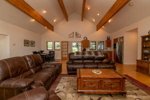 Large great room with amazing cathedral ceilings with wood beams and great natural light as well as interior lighting