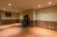Exercise room in basement with 'sport court' style flooring and a woodstove. Crank it up for some hot yoga!