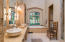 Main floor master bathroom with double vessel vanity, jetted soaker tub, separate shower with bench seat, large custom closet and private water closet.