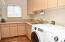 A coveted laundry room with abundant storage, counter space, natural light, and a great laundry sink!