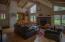 Living room has hardwood floors and wood ceilings, stone fireplace