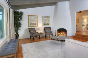 The beautiful living room with vaulted wood ceilings, inviting fireplace and rich wood floors welcomes you in.