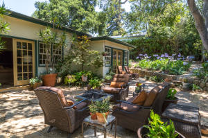 Serene gardens with outdoor seating and fire pit.