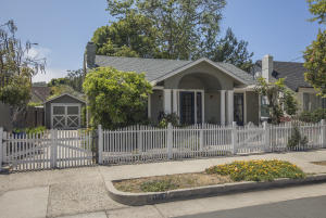 white picket fence and covered front porch on this cozy cottage