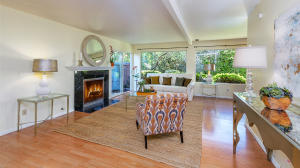 arege inviting living room with fireplace and a wall of glass for enjoying the park-like setting.