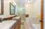 Double vanity, glass door shower and bathtub
