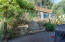Shady back patio with privacy trellis and custom stone bench - ideal location for bbqing.