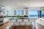A chefs kitchen with expansive center island, wine fridge, pantry and an ocean.