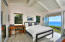 The Primary Ensuite Bedroom also has vaulted ceilings and a glass wall outside the French doors, for maximizing the view.