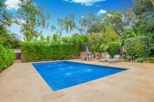 Inviting Pool with built-in BBQ. The private backyard features expansive outdoor spaces and enchanting gardens.