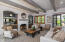 """Beamed ceiling, gas fireplace, wood framed windows and """"Santa Barbara-style"""" French door."""