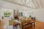 Tall whitewashed timber beams with natural light and hardwood floors.