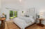 Entry-level primary bedroom with vaulted ceilings & slider to private patio