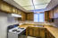 Functional Kitchen with plenty of cupboard space and open bar to living room and dining area.