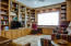 Executive office with custom built shelving and two desk areas.