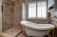Claw soaking tub is fabulous with wall and floor ceramic tile and window perfectly framing the lovely setting outdoors.