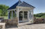 Outside the living space and entertainment options abound. Flagstone patio and short stone walls beautifully accent this amazing Gazebo featuring metal roof, PVC framing and removable screens.