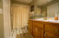 Full bath with tiled flooring, dual sinks, and tub shower combo by both secondary bedrooms.