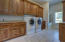 Over sized laundry room with cabinets for storage and dog bath