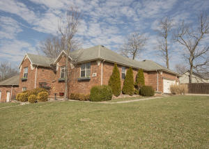 Professional landscaping greats you in this well-crafted, brick home.