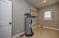 Main floor laundry room off hall near garage with one of the home's three water heaters