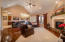 Large open main floor family room with vaulted ceiling, ceiling fan, and fireplace.