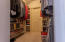 Walk in closet for this bedroom. Door goes to even more storage partially floored.