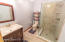 Newly Remodeled Full Bathroom that can be Accessed From the 3 Car Garage Passage or the Exterior Door. Tiled Shower, Glass Doors, Vanity and Tile Flooring.