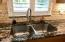 Tiled backsplash, undermounted stainless sink with gooseneck fixture and plantation shutters.