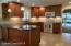 Updated kitchen features polished granite, solid wood cabinets, custom lighting and white appliances for a clean, bright look.