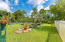 Fenced & Gated Quarter Acre Garden Lined with Plants, Spices, Vegetables and Fruit Trees. Greenhouse with Storage