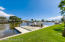 Lawn leads down to the waterfront dock and boat slip with remote control boat lift...