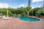 Oversized Paver patio surrounding dark bottom pool with waterfall