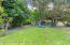 Large, fully fenced backyard with mature tropical foliage, chicken coop and privacy!