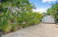 Rear driveway with mature landscaping, 12x10 shed and private gate.