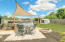 Backyard patio and firepit with sunsail offer shade on hot sunny days.