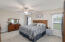 Spacious owner's suite with ceiling fan and ensuite bathroom.