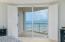Plantation shutters and sliders lead to balcony with spectacular view