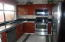 Kitchen has tile floors and stainless steel appliances. Counter top is granite squares.